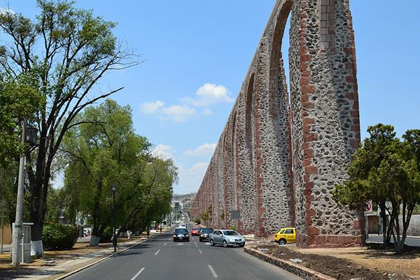 View of an avenue in Queretaro, Mexico lined with a stone aqueduct on one side and green trees on the other