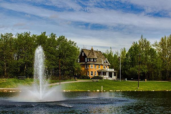 A fountain spouts water in front of a beautiful property in Red Deer, Alberta