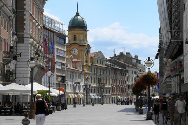 Pedestrians stroll through the historic streets of Rijeka, Croatia