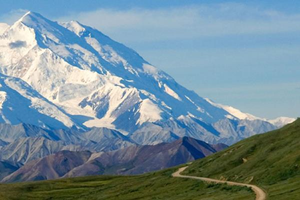 Dirt road leading to Mount Denali in Alaska on a clear day