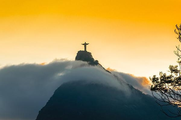 Christ the Redeemer statue stands above the clouds at sunset in Rio de Janeiro, Brazil