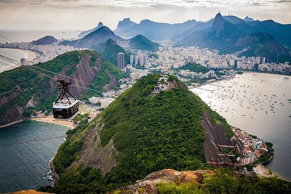 Aerial view of Rio de Janeiro, Brazil with a cable car, mountains, buildings and beaches in frame