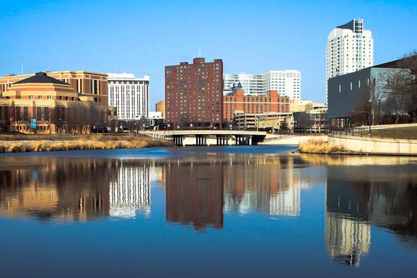 The tall buildings of downtown Rochester, Minnesota reflect off of calm blue waters