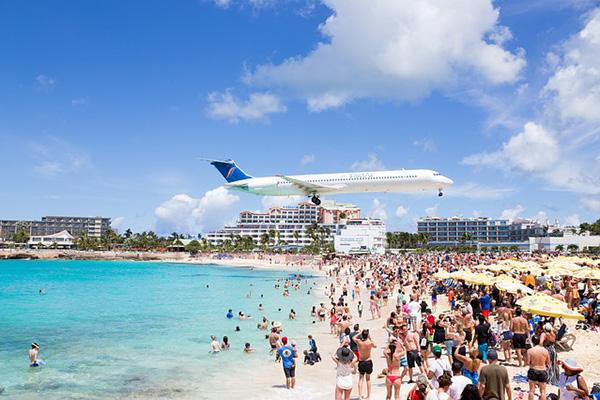 Sunseekers watch as a plane heads in for a landing over Maho Beach in Saint Martin