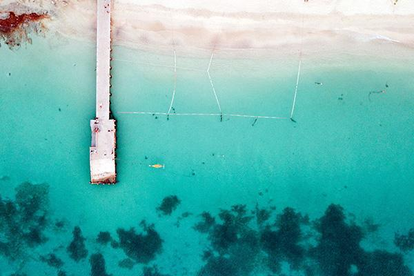 An aerial view of a dock jutting out to sea on a beach in Saint Martin