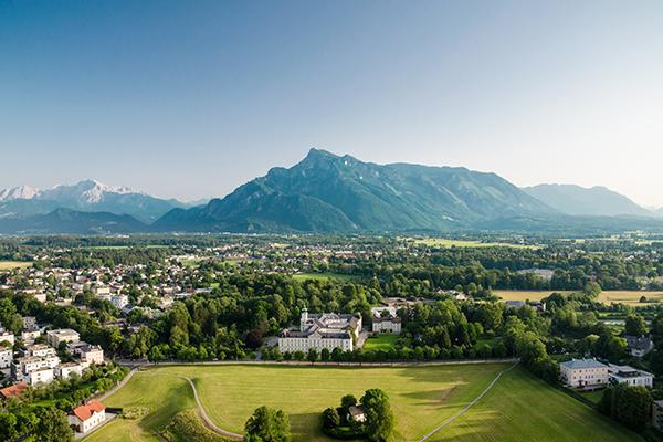 A birds eye view of tree-filled, mountainous Salzburg, Austria in summer