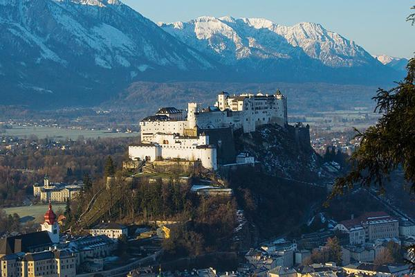 A fortress stands tall over Salzburg with mountains in the background