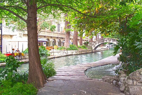 The inviting River Walk leads under thick, vibrant trees toward a beautiful stone bridge in San Antonio, Texas