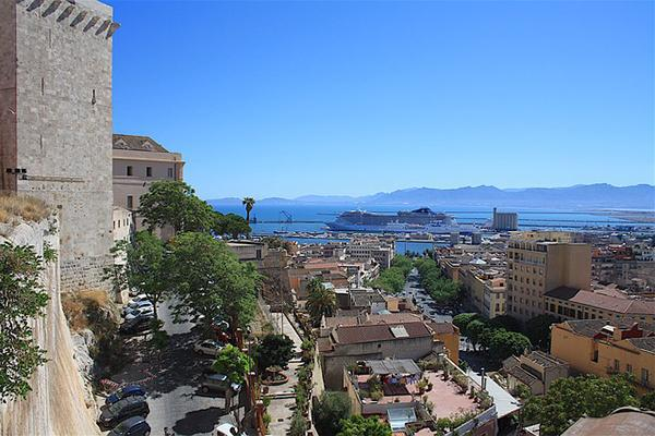 Mediterranean buildings fill the foreground with a docked cruise ship off in the distance