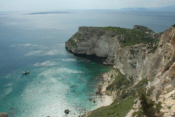 A cliff juts out dramatically toward the sparkling Sardinian coast in Cagliari, Italy