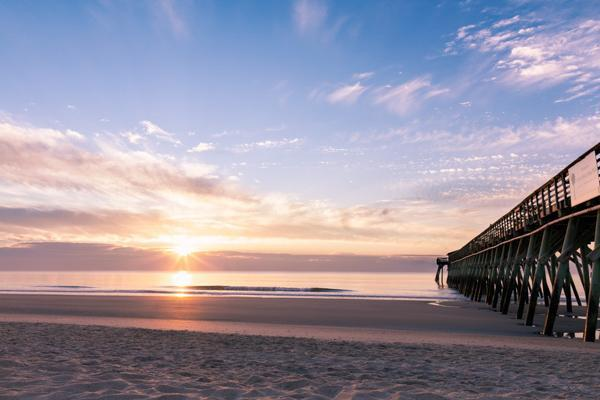 The sun sets on a beachside pier in Myrtle Beach, South Carolina