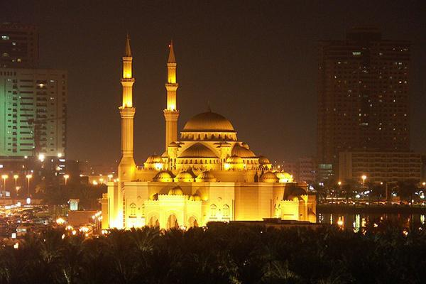 A beautiful mosque lights up the night in Sharjah, United Arab Emirates