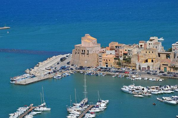 A collection of medieval buildings jut out onto the Mediterranean coast of Trapani, Sicily in Italy