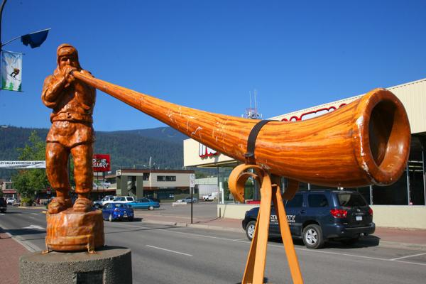 A carved wooden statue of a man bellowing through a Flugelhorn welcomes visitors to Smithers, Canada