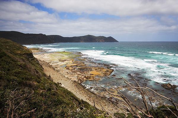 The aqua-coloured waters of Tasmania crash to the shore of South Cape Bay