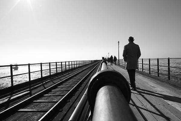A man walks across the Southend Pier (black and white image), in Southend-on-Sea, UK