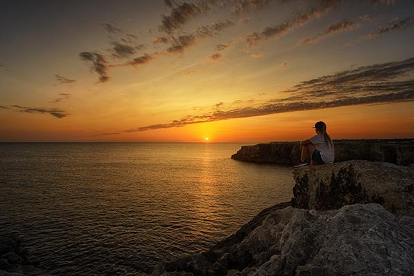 A woman sits on a rock, watching the sunset in Menorca, Spain