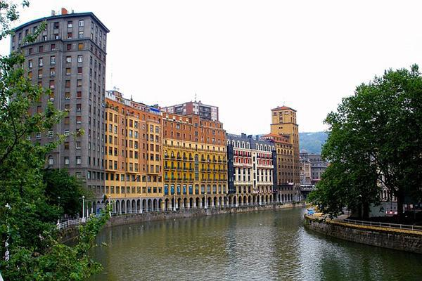 A building-flanked canal runs through the city of Bilbao on a moody day in Spain