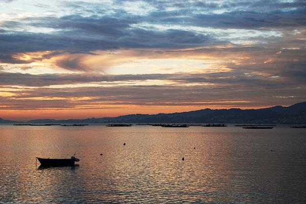 Colours dance across the sky at sunset over the ocean near Vigo, Spain
