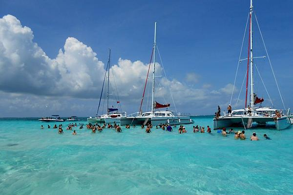 Catamarans full of tourists gather at Stingray City in the Grand Cayman islands