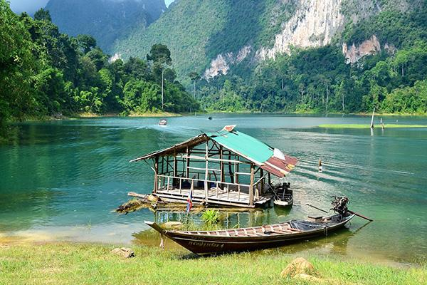 A small boat rests on the water's edge at the tranquil Khao Sok National Park