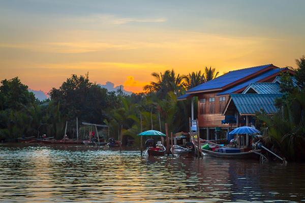 The sun sets on an idyllic river setting in Surat Thani, Thailand