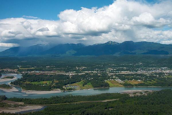 Aerial view of the town of Terrace, British Columbia, with mountains behind and a river in front