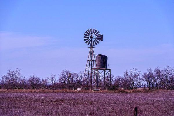 An old windmill sits motionless at dusk in a farm field in Abilene, Texas