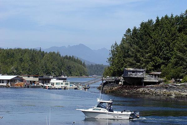 A boat cuts across the water at Tofino Harbour in British Columbia, Canada