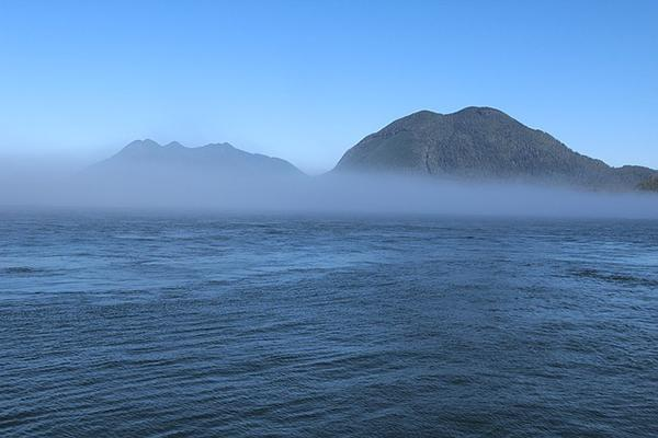 Fog rolls in over the sea and mountainous landscape near Tofino, British Columbia