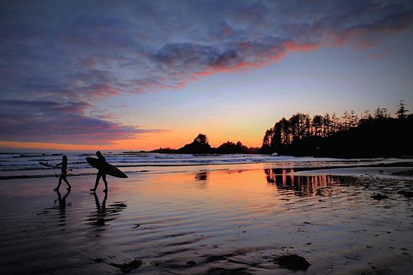 A pair of surfers walk the beach at sunset in Tofino, British Columbia