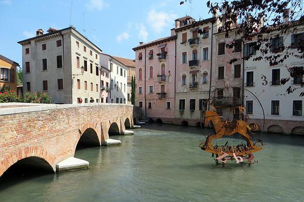 A canal bridge leading to old residential buildings in Treviso, Italy