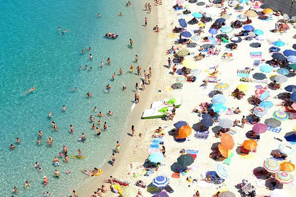 Sunseekers crowd the beach and turquoise waters of Tropea, Calabria, Italy