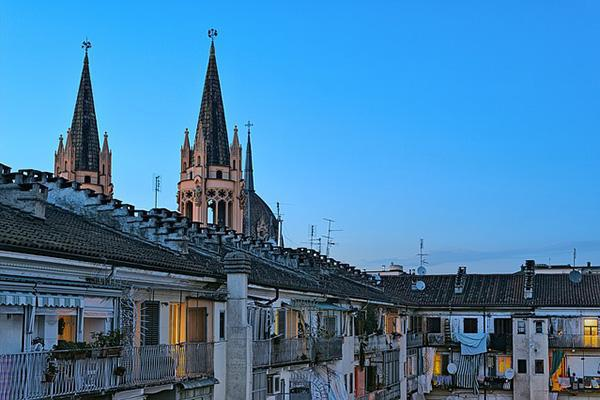 Two church spires reach up over a residential apartment building in Turin, Italy