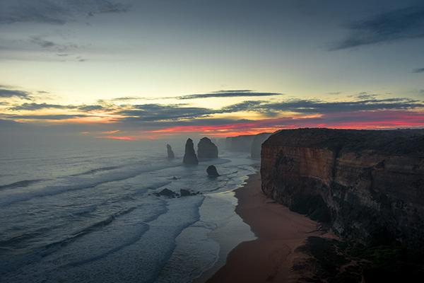 Waves crash the shores of the Great Ocean Road as they roll past the Twelve Apostles and the sun sets on the horizon