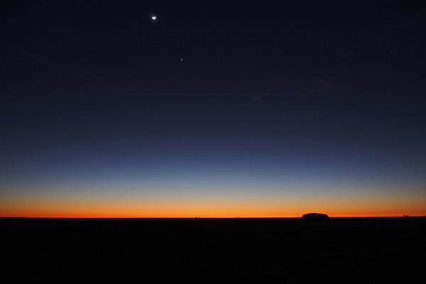 The vast emptiness of the Australian Outback contrasting with Uluru meeting the setting sun in Uluru-Kata Tjuta National Park