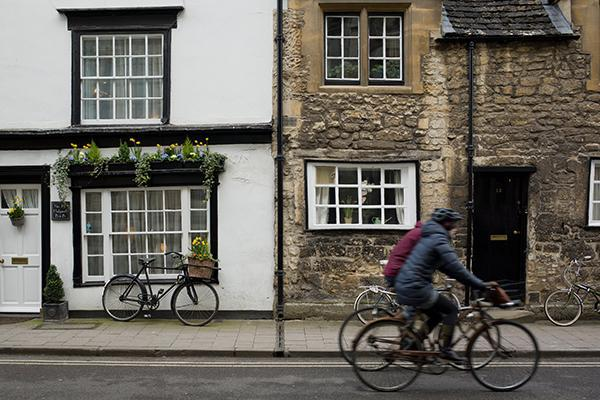 Cyclists ride by quaint houses in Cambridge, England