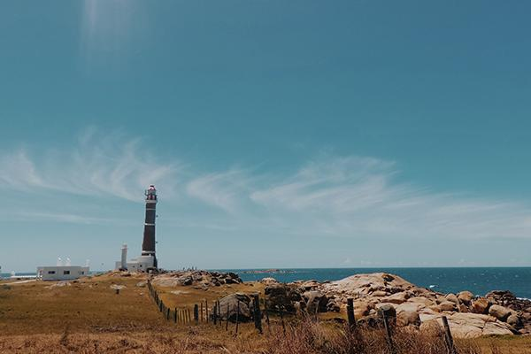 A lighthouse reaches up to the blue skies of Cabo Polonio, Uruguay