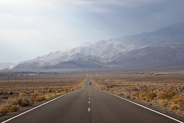 A stretch of highway leads toward the mountains in Death Valley National Park, USA