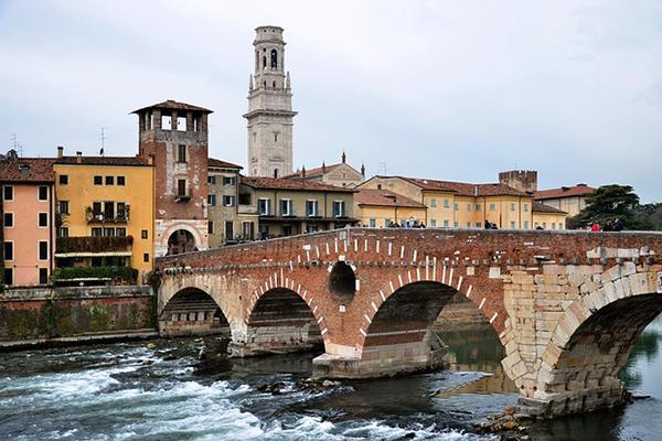 A stone bridge over a rushing river in Verona, Italy