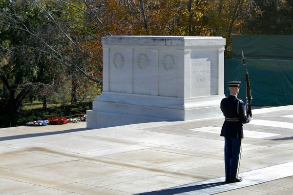 A soldier stands at attention besides the Tomb of the Unknown Soldier in Arlington, Virginia