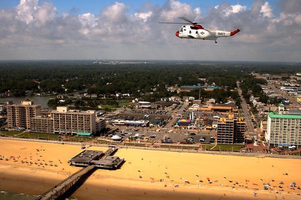 A Navy helicopter flies over beach-goers near a pier at Virginia Beach, Virginia