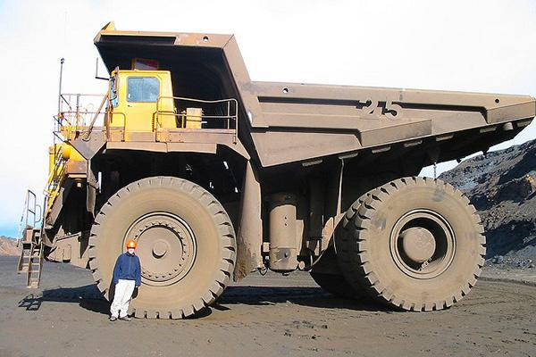 A mining employee stands in front of a huge mining truck in Wabush, NL, Canada