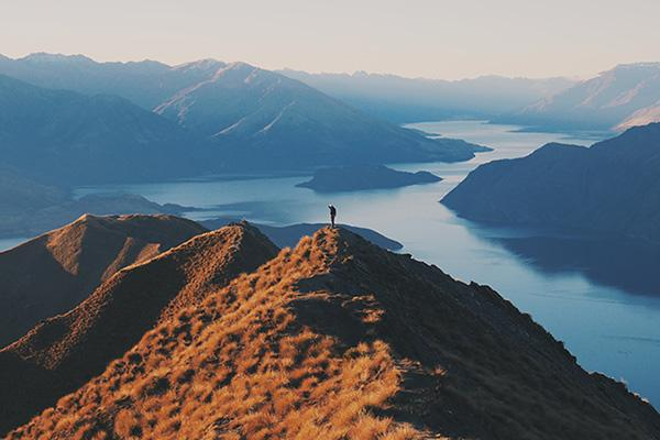 An adventurous hiker stands atop Roy's Peak, admiring the beautiful scenery near Wanaka, New Zealand