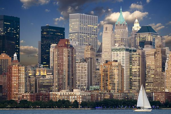 A sailboat floats by New York City, New York
