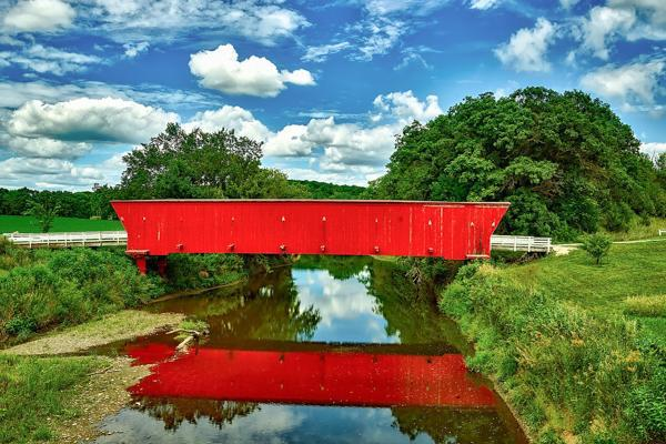 An iconic red covered bridge spans the width of a small river in Madison, Wisconsin