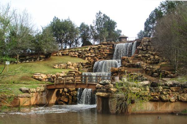 Waterfalls cascade down a rocky hillside in Lucy Park, Wichita Falls, Texas