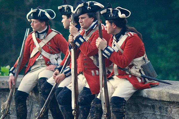 Reenactment soldiers sit together in uniform at Colonial Williamsburg