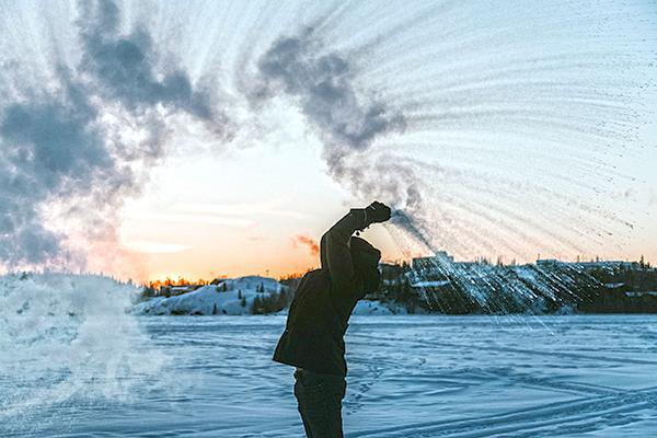 A visitor to Yellowknife, Northwest Territories throws hot water into the frigid Canadian winter air, which freezes instantly
