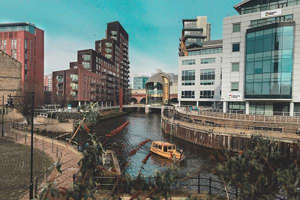 A transport boat heads down a canal flanked by buildings in Leeds, United Kingdom